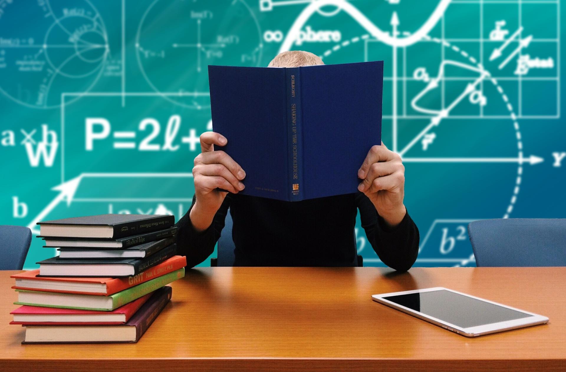 Učenik sjedi u školskoj klupi s knjigom